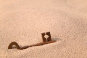 Rusty old key in sand